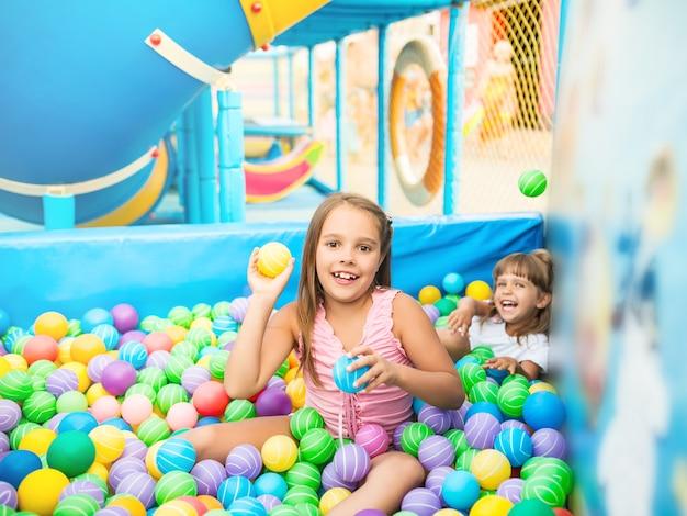 Duas garotas brincando na piscina com bolas de plástico coloridas na sala de jogos.