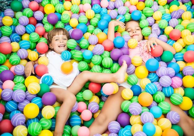 Duas garotas brincando na piscina com bolas de plástico