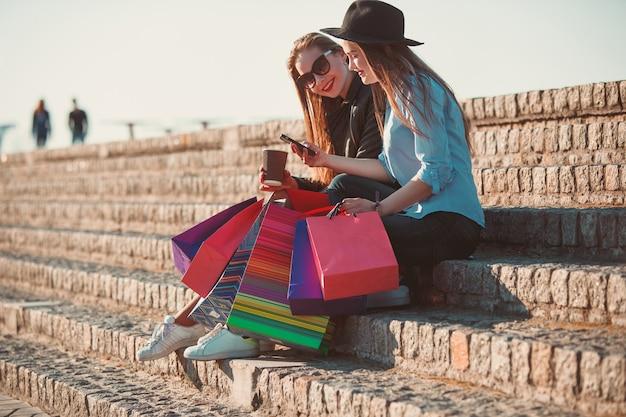 Duas garotas caminhando com compras nas ruas da cidade