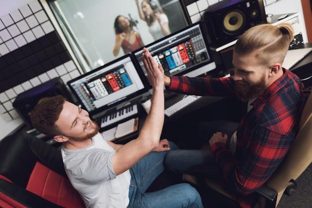 Duas garotas cantam no estúdio de gravação.