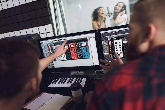 Duas garotas cantam no estúdio de gravação