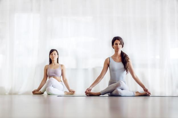 Duas garotas caucasianas atraentes focadas na posição da pilha de joelho. interior do estúdio de ioga.