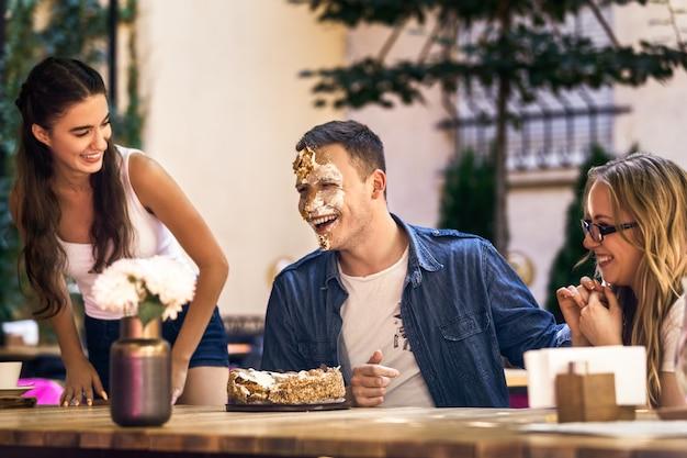 Duas garotas caucasianas e um cara com o rosto sujo com creme de bolo estão rindo e sentados ao redor da mesa ao ar livre