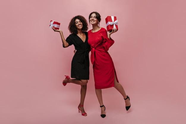 Duas garotas charmosas e elegantes com cabelos castanhos em elegantes vestidos de bolinhas vermelhas e pretas e saltos altos segurando caixas de presente, sorrindo e se abraçando