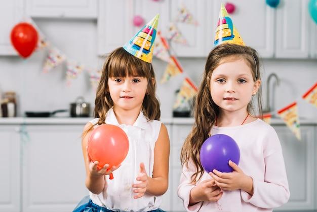 Duas garotas com balões vermelhos e roxos na cozinha