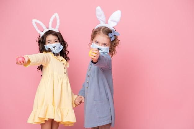 Duas garotas com bandana de orelhas de coelho e máscara protetora com ovos coloridos em fundo rosa. covid conceito de páscoa.