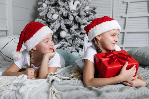 Duas garotas com bonés vermelhos deitar em uma cama com caixas de natal no contexto de uma árvore de ano novo.