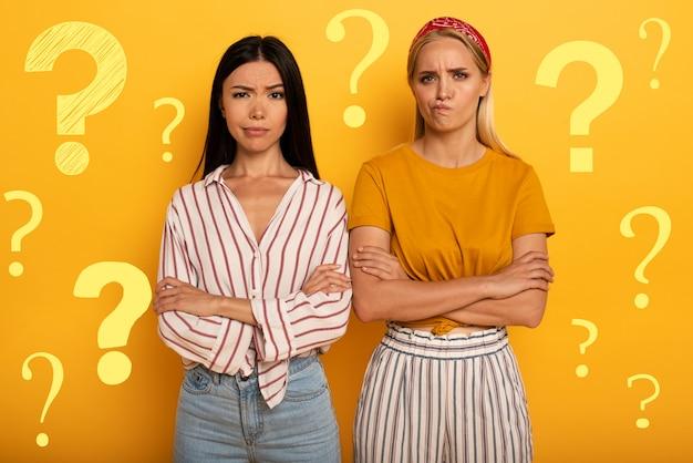 Duas garotas com expressão perturbada têm dúvidas sobre algo