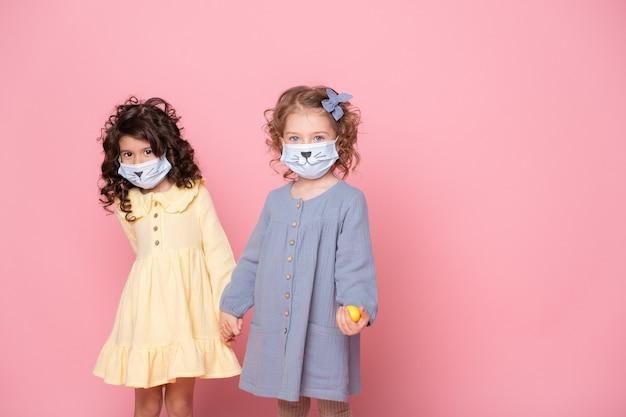 Duas garotas com máscara protetora com ovos coloridos de mãos dadas sobre fundo rosa