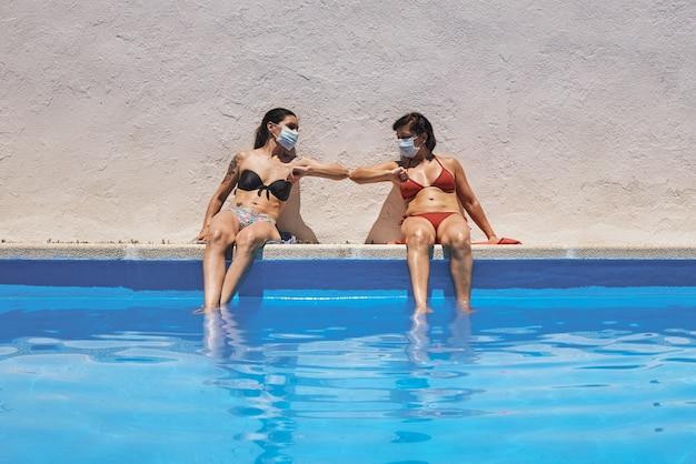 Duas garotas com máscaras sentadas na piscina tomando banho de sol se cumprimentam