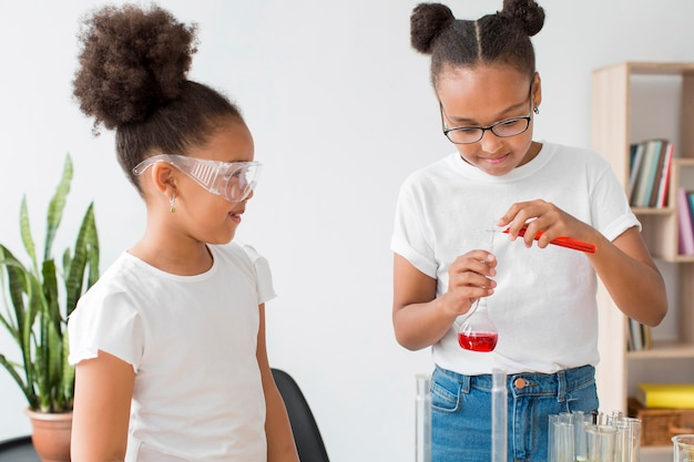 Duas garotas com óculos de segurança carregando experimentos científicos