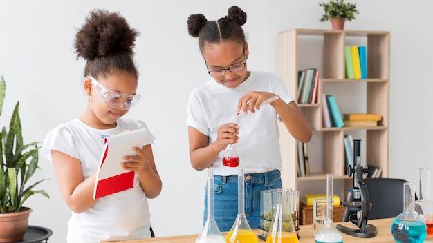 Duas garotas com óculos de segurança carregando experimentos de química