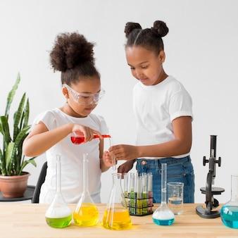 Duas garotas com óculos de segurança, experimentando a ciência