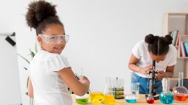 Duas garotas com óculos de segurança, experimentando química e poções