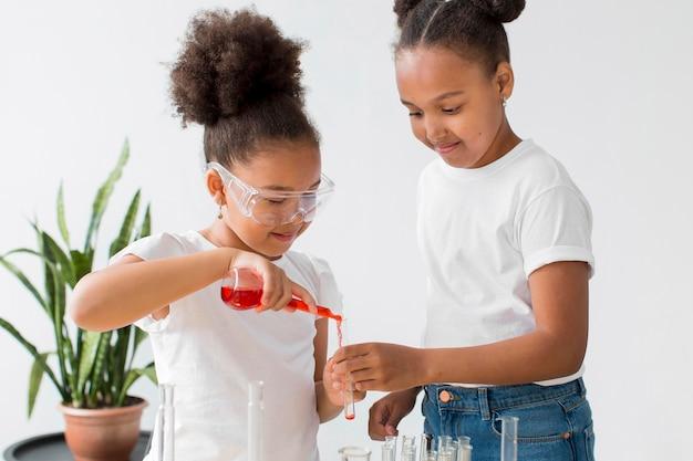 Duas garotas com óculos de segurança, experimentando química
