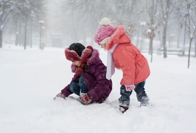 Duas garotas com roupas de inverno diferentes estão procurando algo na neve no parque durante uma nevasca
