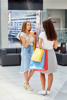 Duas garotas com sacos de compras conversando