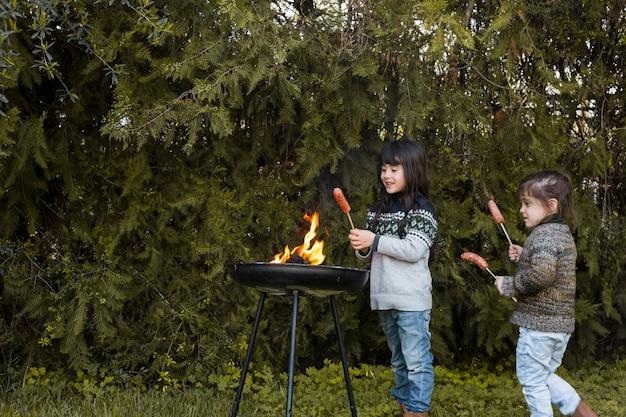 Duas garotas com salsichas em pé perto de churrasco