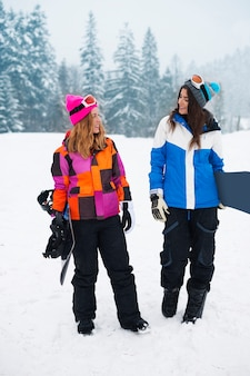 Duas garotas com snowboards no inverno