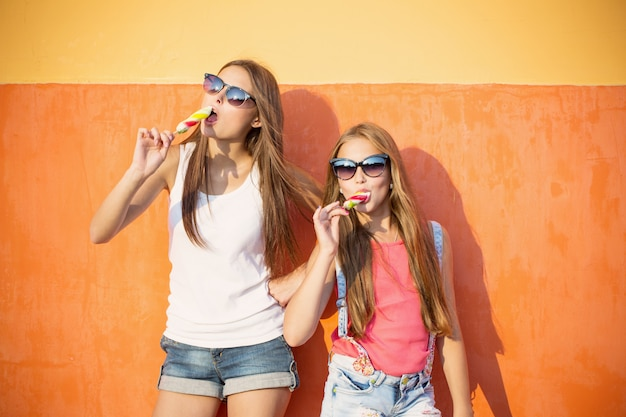 Duas garotas com sorvete na parede do fundo