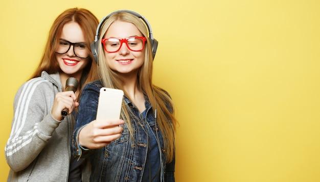Duas garotas com um microfone cantando e se divertindo juntas, fazem selfie