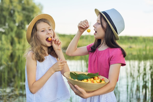 Duas garotas comendo cerejas amarelas, dia de verão na natureza