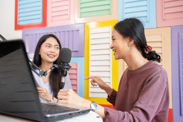 Duas garotas conversando durante o podcast usando um laptop e um microfone