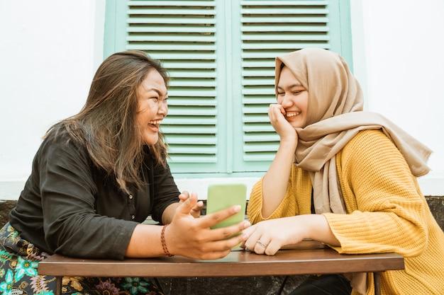 Duas garotas conversando em um café enquanto segura o celular