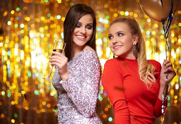 Duas garotas dançando na parede de purpurina