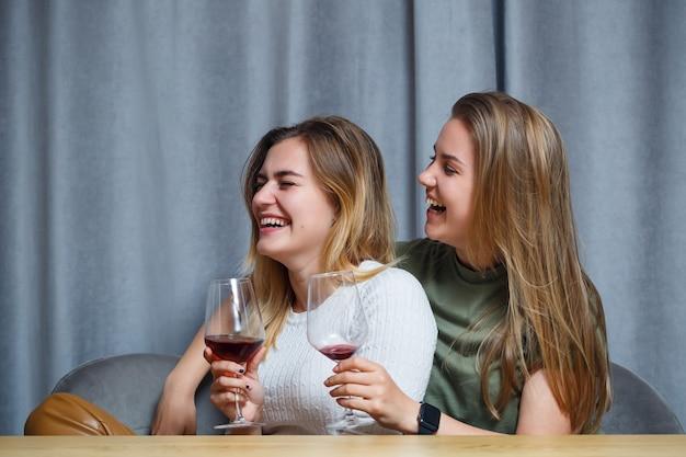 Duas garotas de aparência europeia com cabelos loiros estão sentadas à mesa, bebendo vinho e rindo, relaxando em casa, álcool