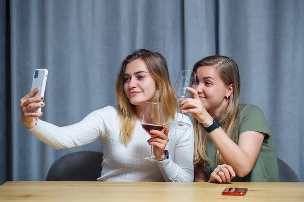 Duas garotas de aparência europeia estão sentadas à mesa com taças de vinho. conversa de namoradas com bebidas alcoólicas.
