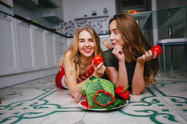 Duas garotas de esportes em uma cozinha com legumes