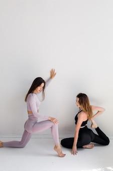 Duas garotas de esportes posando isoladas em um fundo branco fitness modelo mulher em estúdio com espaço de cópia foto de alta qualidade