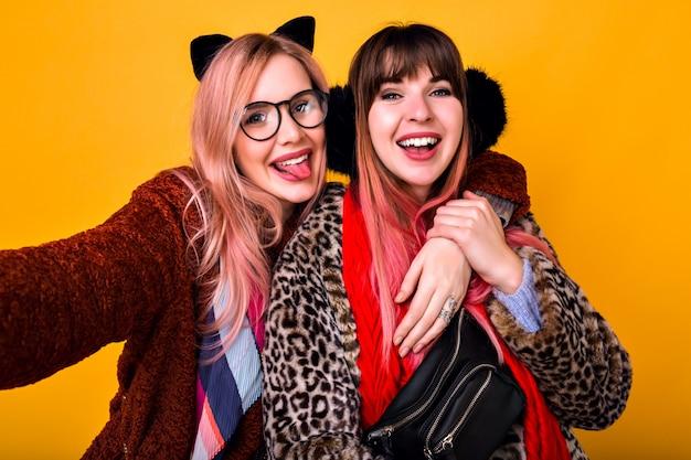 Duas garotas de irmã de melhores amigos hipster muito engraçado fazendo selfie na parede amarela, mostrando a língua e sorrindo, vestindo casacos de pele estampados de primavera na moda, lenços, bolsa de traseiro e óculos transparentes.