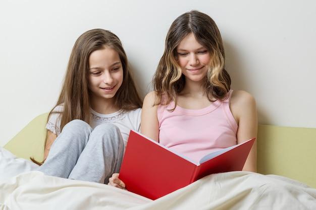 Duas garotas de irmã sentada em casa na cama