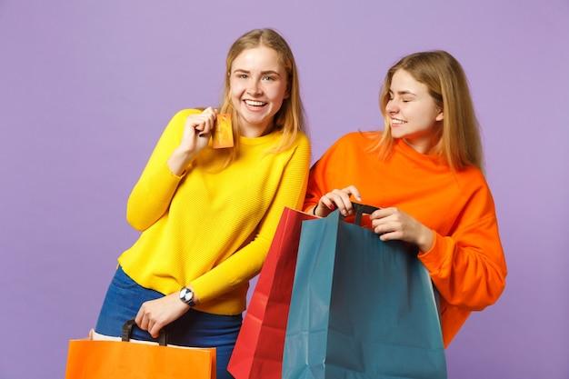 Duas garotas de irmãs gêmeas loiras rindo em roupas vivas segurar o cartão do banco de crédito, saco do pacote com compras depois de fazer compras isoladas na parede azul violeta. conceito de família de pessoas.