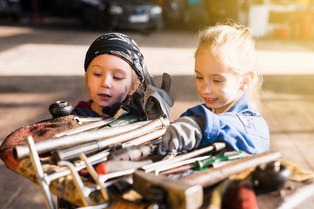 Duas garotas de macacão, escolhendo ferramentas