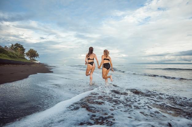 Duas garotas de maiô correndo na praia