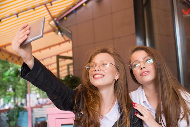 Duas garotas de óculos fazendo uma selfie no café de verão