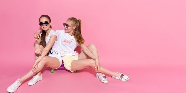 Duas garotas de skate enlouquecem e se divertem juntas. mulheres bonitas e desportivas, emoção positiva. fundo rosa.