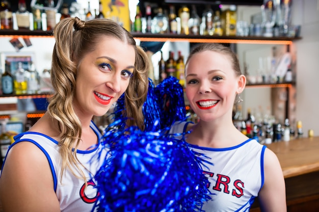 Duas garotas de torcida no bar de esportes