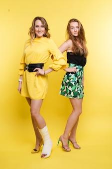 Duas garotas de vestido amarelo. menina sorridente, olhando para a câmera, posando com a perna quebrada em gesso.
