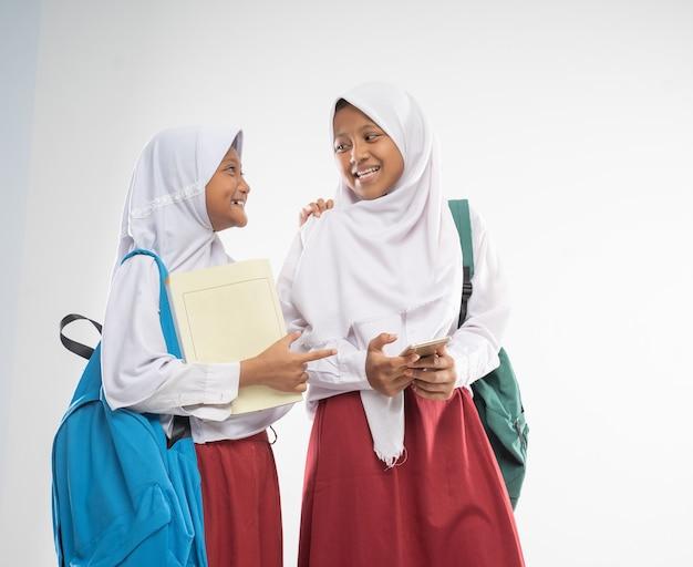 Duas garotas de véu usando uniformes do ensino fundamental conversando com mochilas e um livro