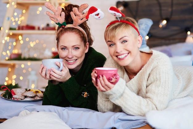 Duas garotas deitadas na cama bebendo chá