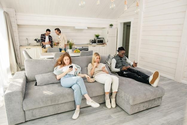 Duas garotas e um cara com smartphones relaxando no sofá com pipoca e vinho enquanto seus amigos conversam