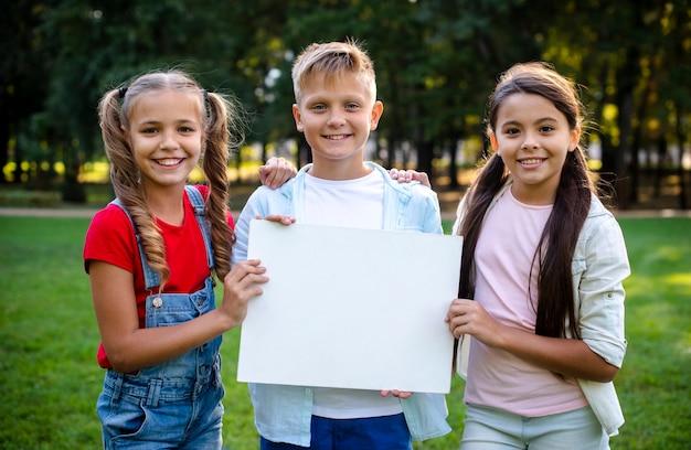 Duas garotas e um garoto segurando um cartaz nas mãos