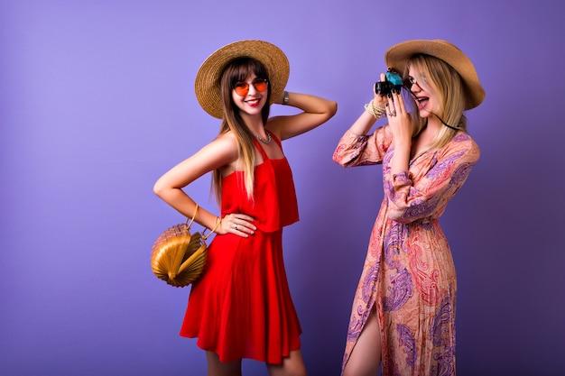 Duas garotas elegantes e hipster se divertindo juntas, chapéus e acessórios vintage boho, mulher loira fazendo fotos de sua melhor amiga,