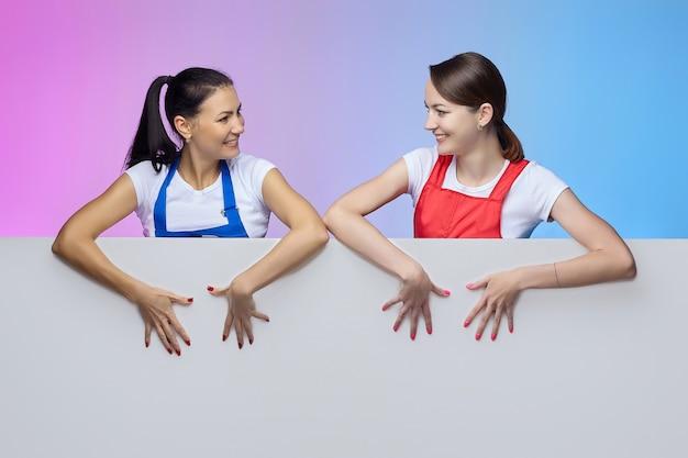Duas garotas em aventais posam com um outdoor branco. conceito de publicidade