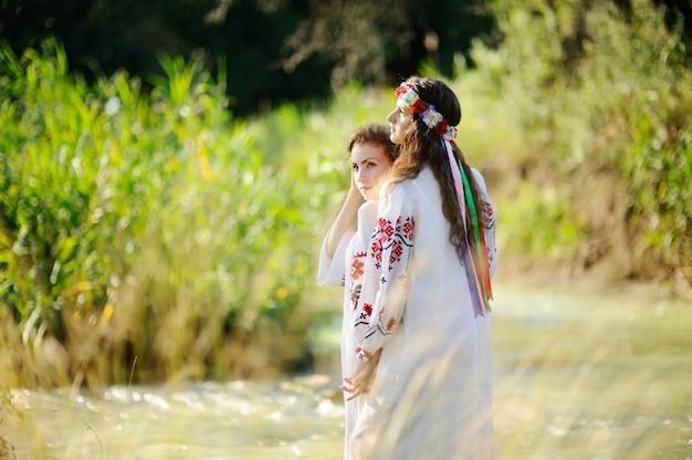 Duas garotas em camisas ucranianas estão no fundo do rio