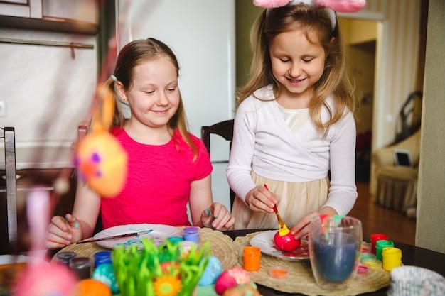 Duas garotas em casa na cozinha da mesa pintam ovos de páscoa com tintas.